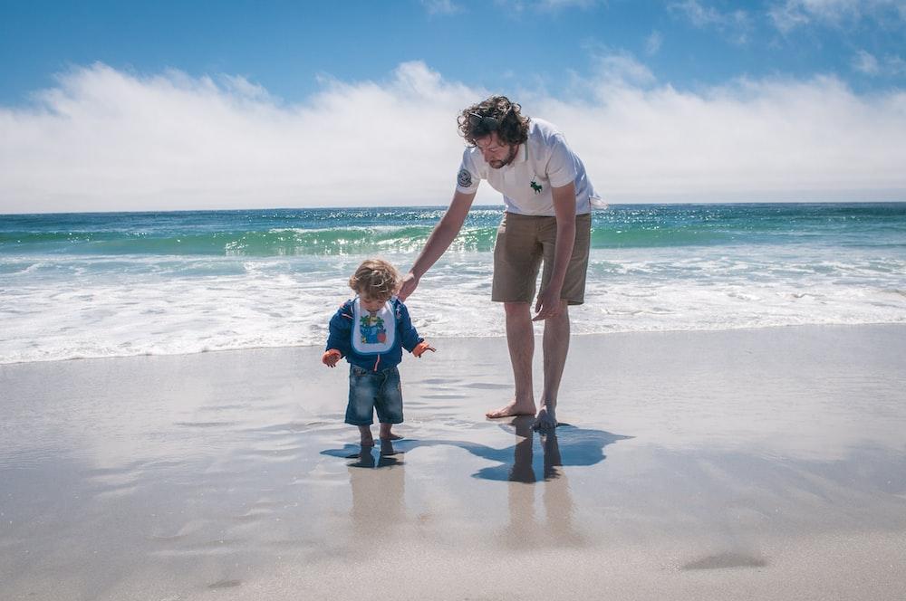 man and boy walking beside beach