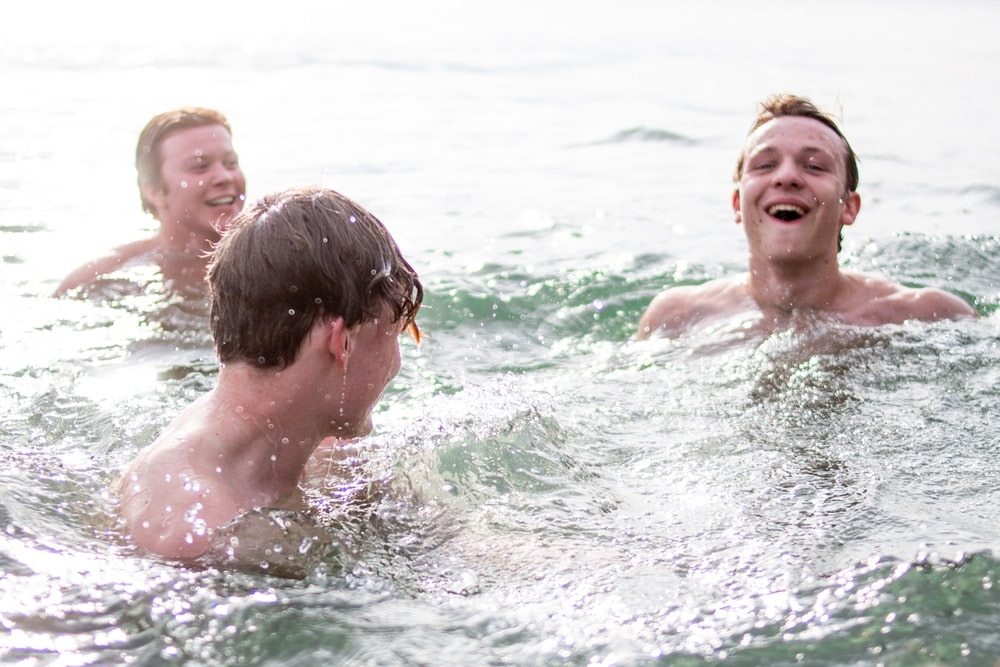 three men smiling while swimming during daytime