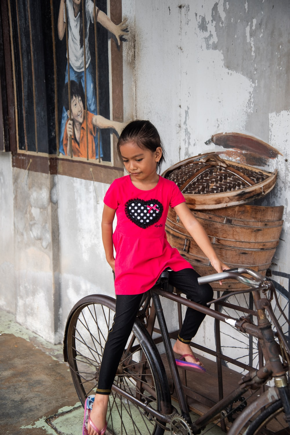 girl sitting on bicycle near wall during daytime