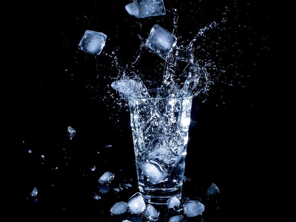 ice cubes dropped in clear drinking cup with water