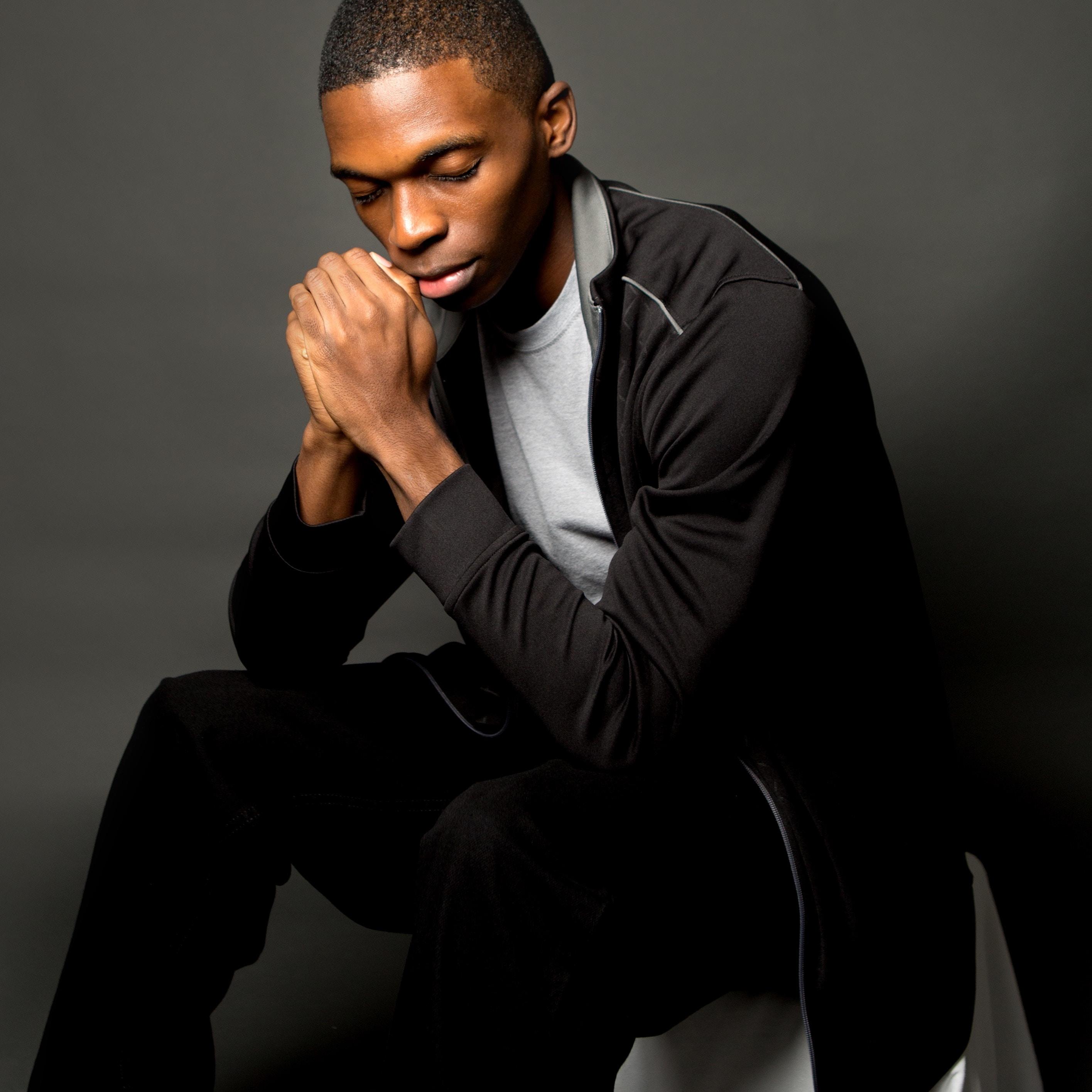 man sitting in black zip-up jacket