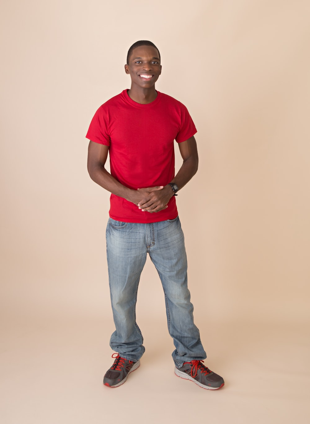 smiling man wearing red crew-neck t-shirt and gray denim jeans