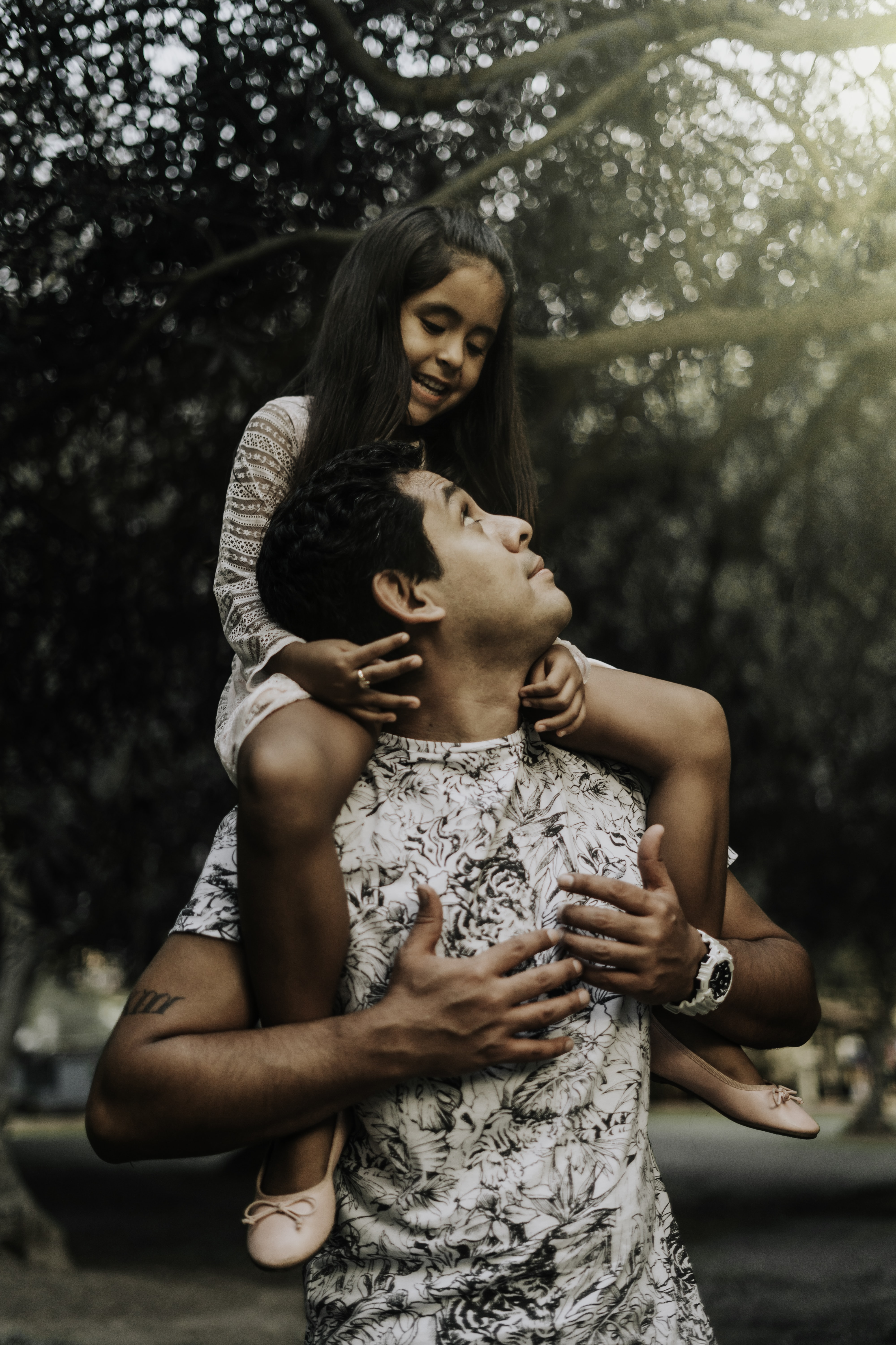 girl riding on his father's back
