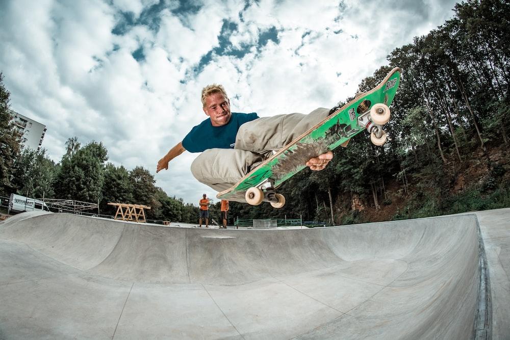 man riding green skateboard on skate park during daytime