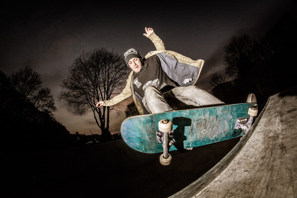 man playing skateboard on focus photography