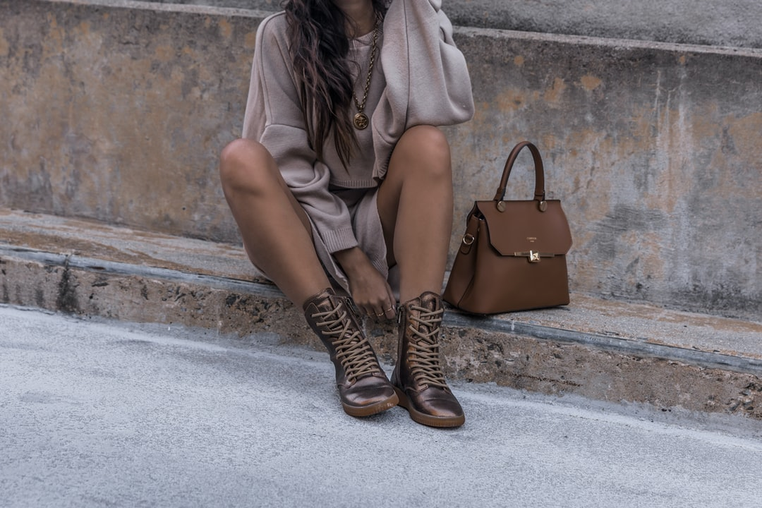 Girl sits on a cement street curb wearing a sweater dress and metallic copper hiker boots with a luxury handbag. Neutral beige tones are great for overlaying white fonts or graphics.