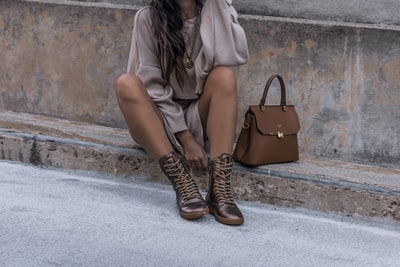 Please help support by following @dayinmydreams on Instagram xoxo Girl sits on a cement street curb wearing a sweater dress and metallic copper hiker boots with a luxury handbag. Neutral beige tones are great for overlaying white fonts or graphics.