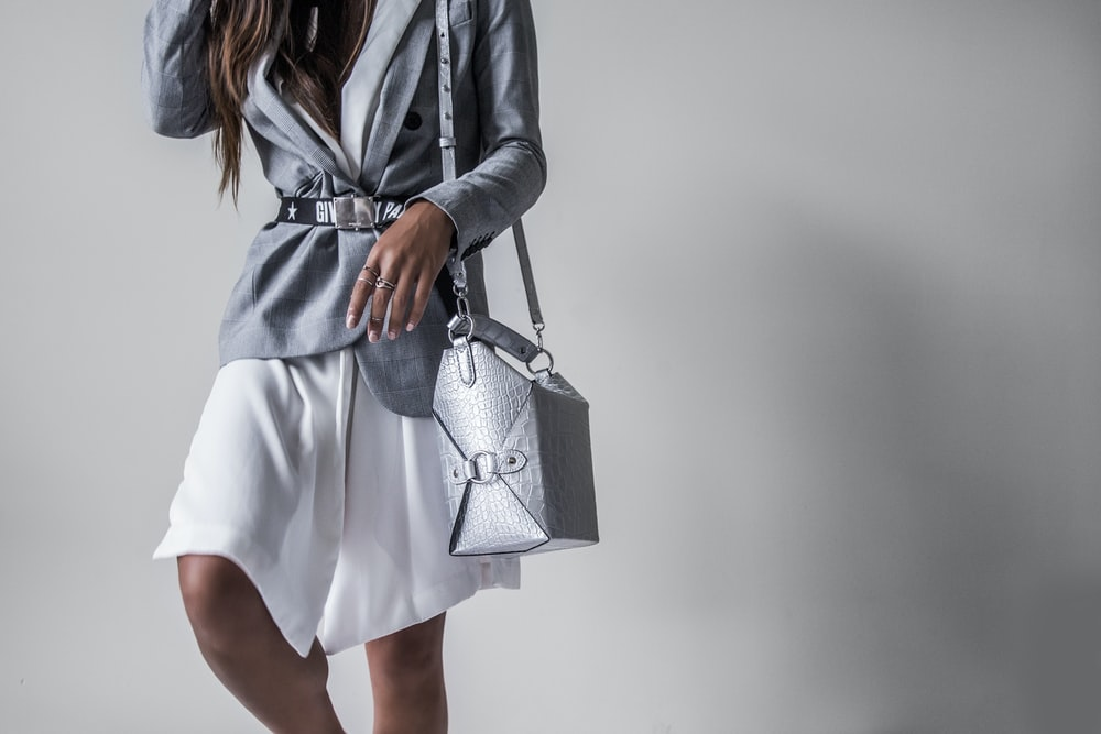 standing woman in white skirt with gray leather shoulder b