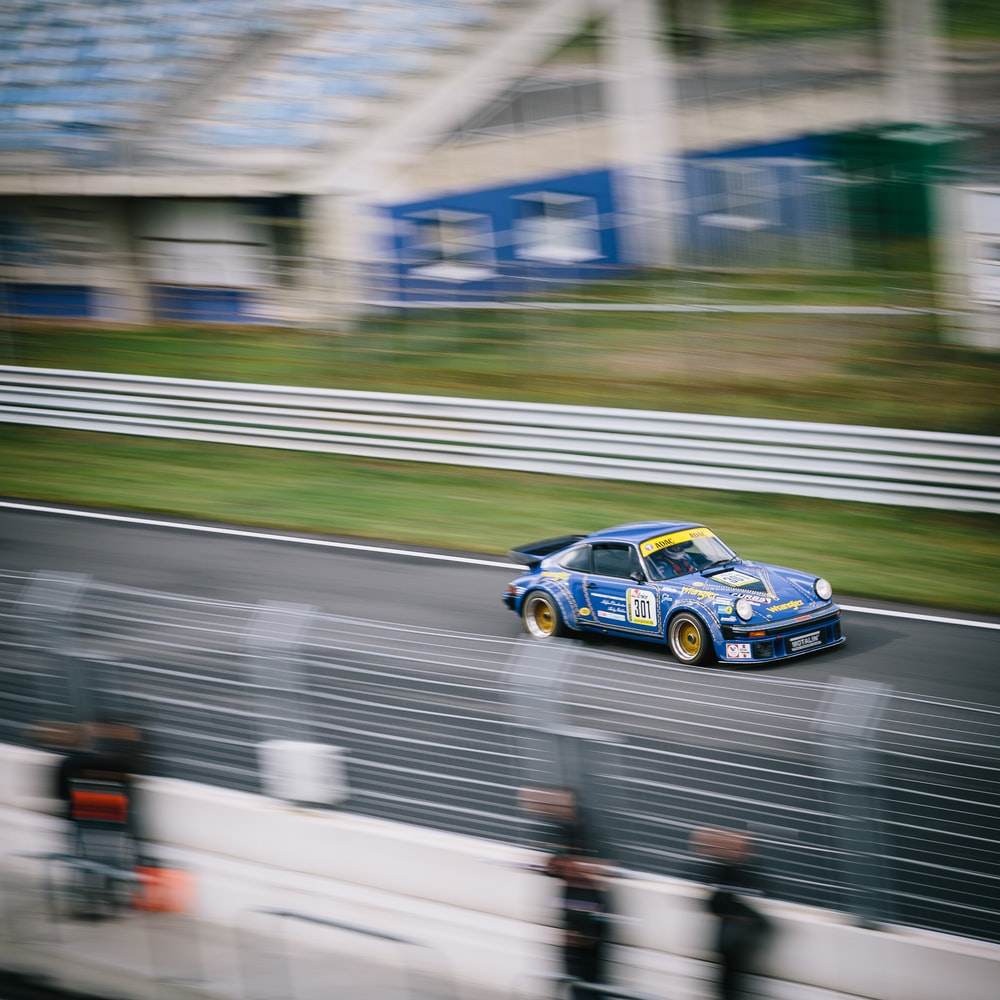 blue NASCAR car on paved road