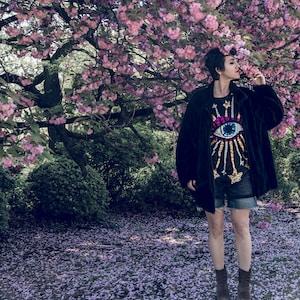 woman standing under cherry blossom tree
