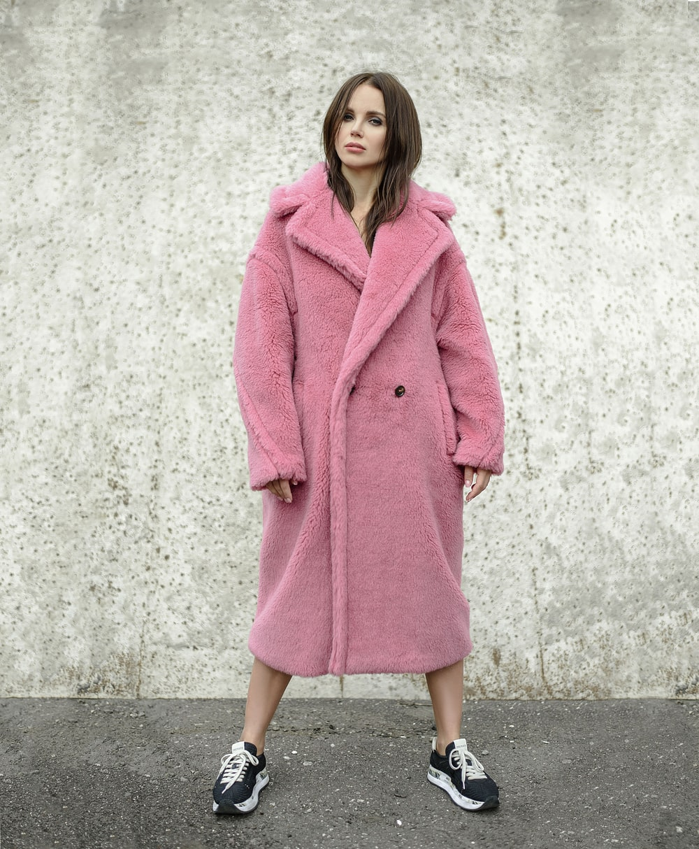 woman standing while wearing pink coat