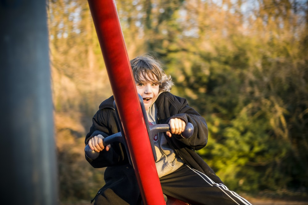 selective focus photography of boy riding on swing