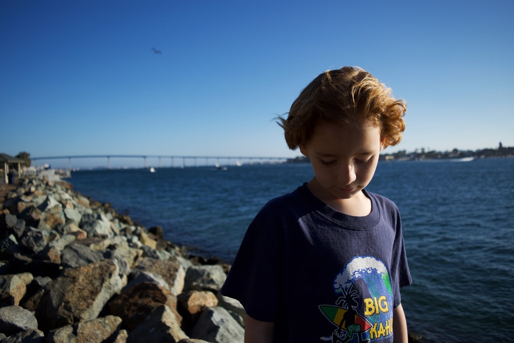 boy standing on rocking shore while looking down