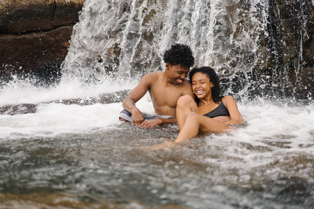 smiling topless man sitting near smiling woman beside waterfalls