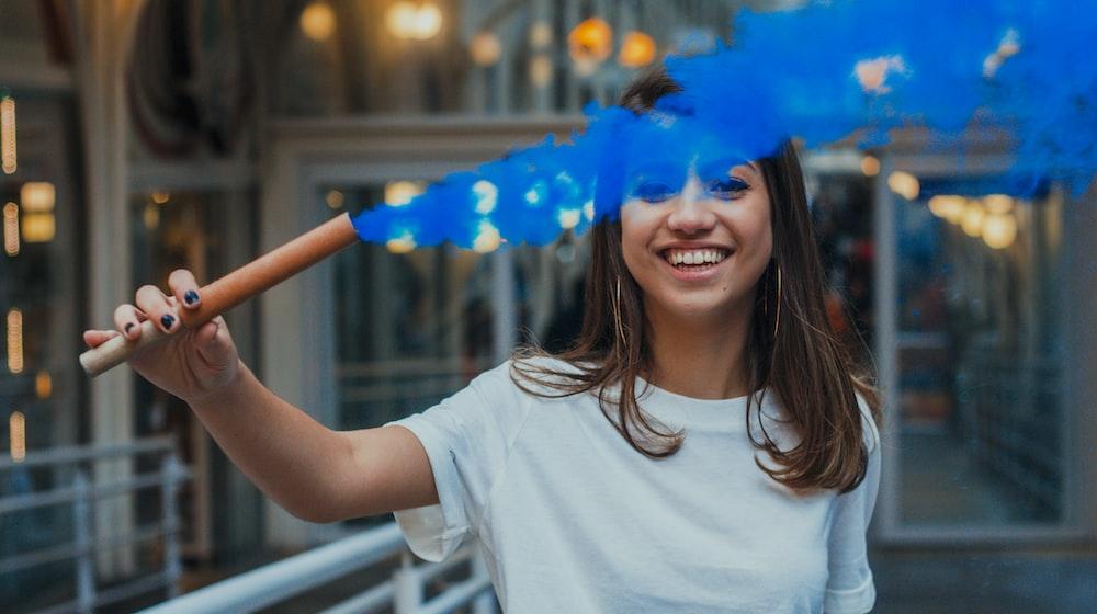 woman holding stick with blue smoke