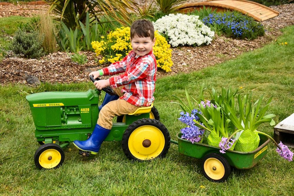 boy riding riding mower toy