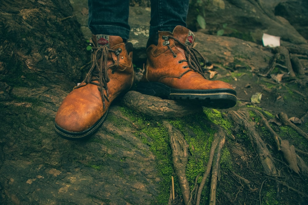 person in brown work boots on top of tree root