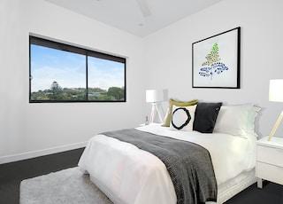 white bedspread on bed near window