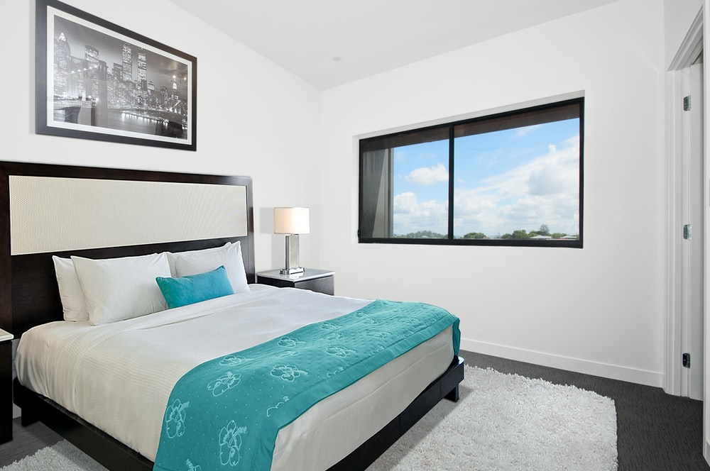 white bedspread and black wooden bed