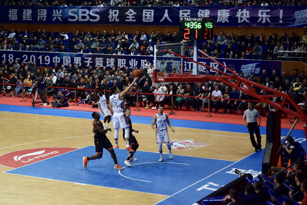 men playing basketball game surrounded with people watching