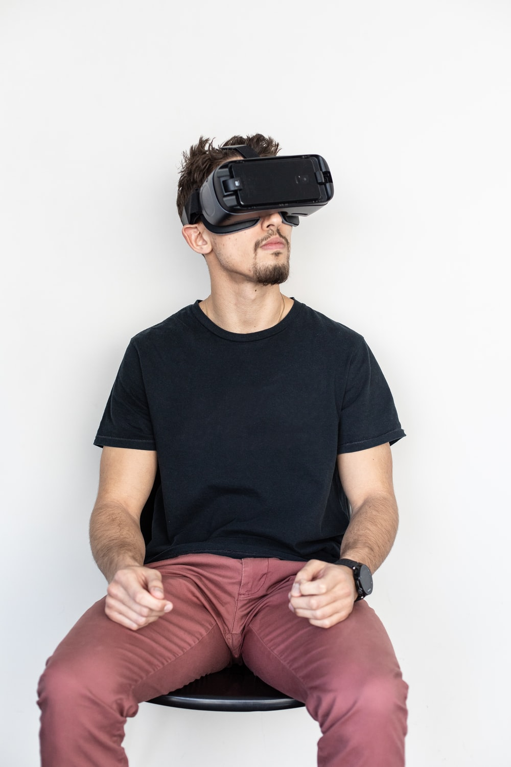 man sitting and using black virtual reality headset