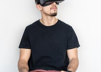 男子坐和使用黑色虚拟现实耳机