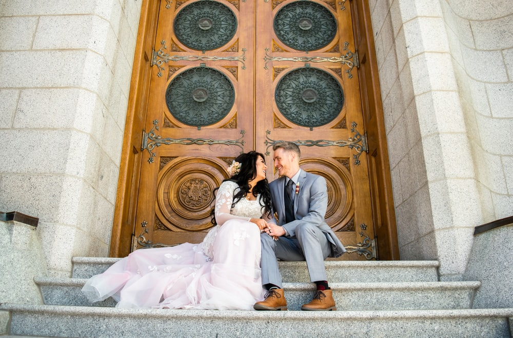 married couple sitting in front close door
