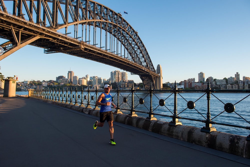 man wearing blue tank top running under bridge
