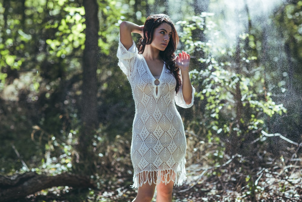 woman wearing V-neck half-sleeved dress standing in jungle during daytime