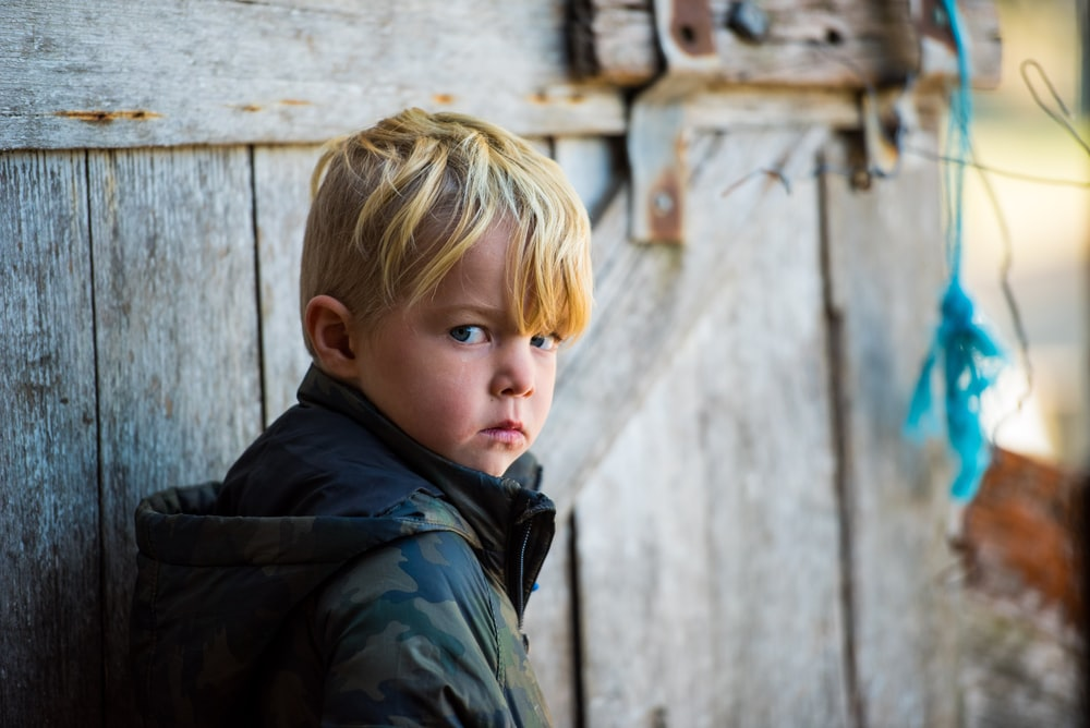 shallow focus photo of boy in green and black woodland camouflage hoodie