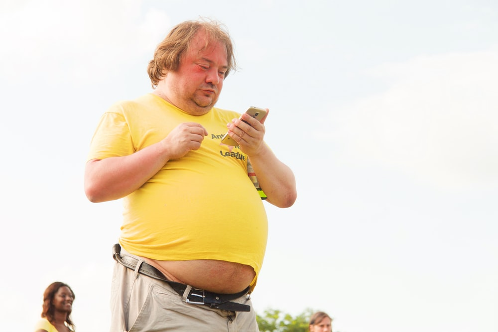 man in yellow shirt and brown pants using smartphone