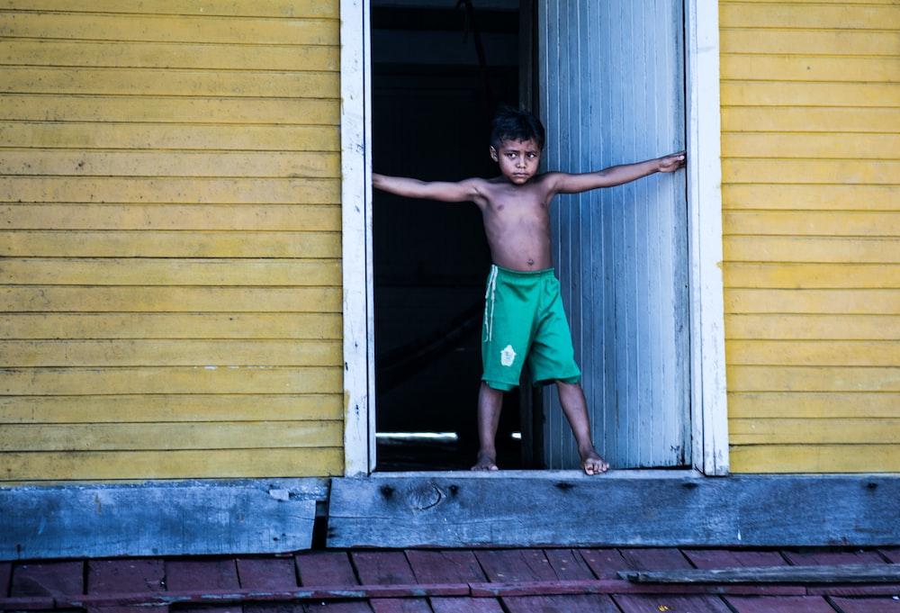 topless boy wearing green shorts standing beside door