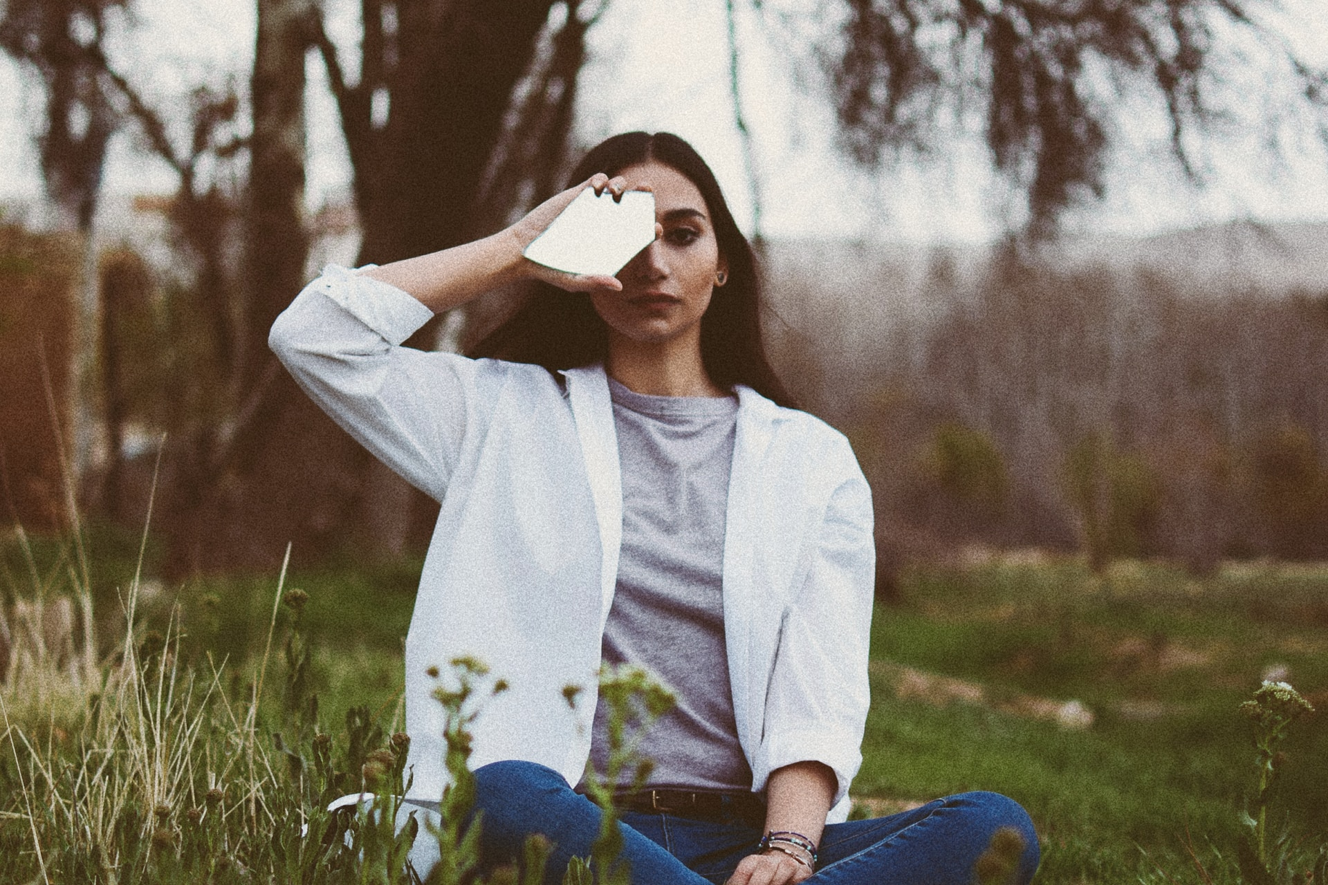 woman in white jacket sitting on grass