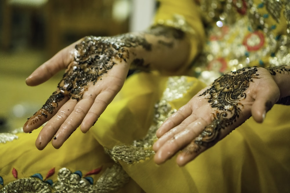 person's hands with mehndi tattoos