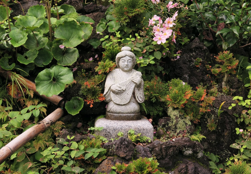 woman playing guitar mini statue near flower garden