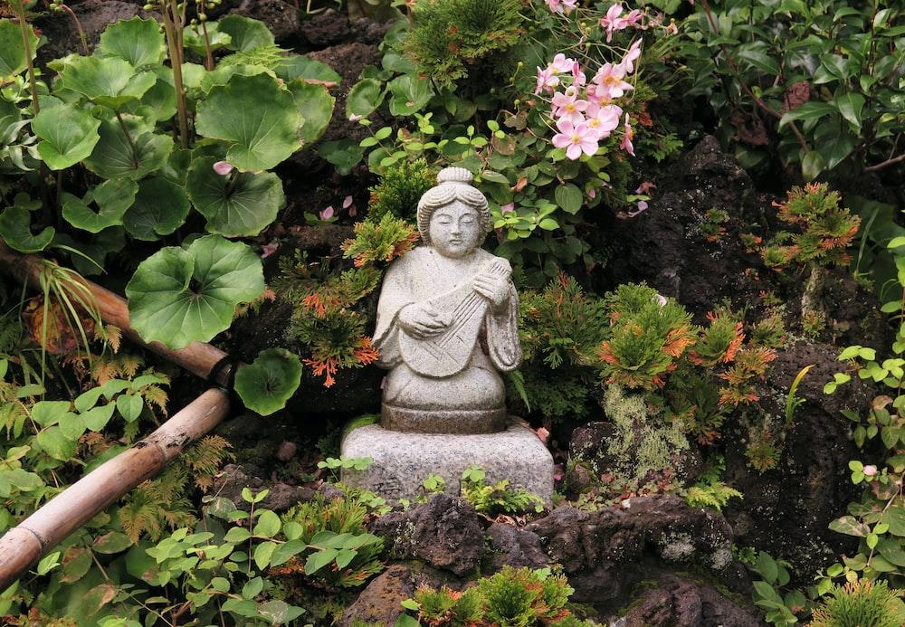 woman playing guitar mini statue near flower garden
