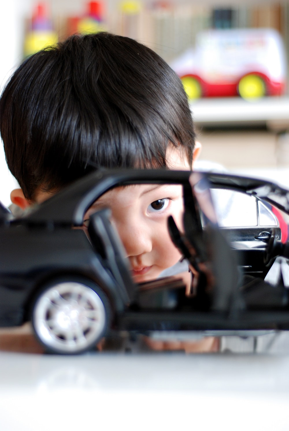 boy playing with car toy