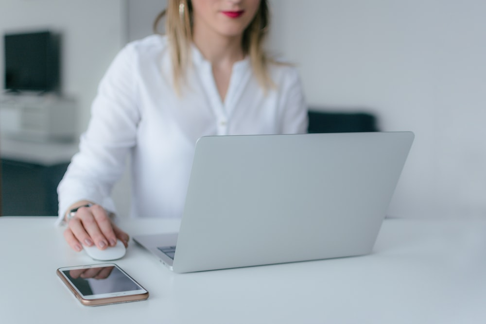 woman sitting and using MacBook Air and Apple Magic mouse
