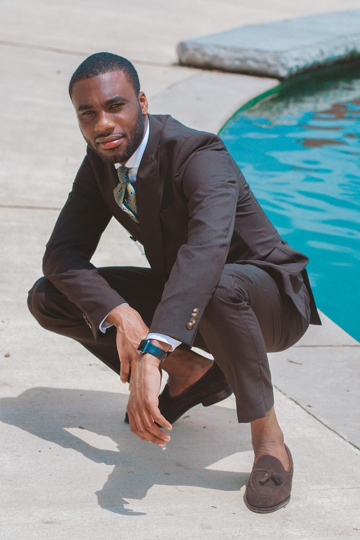 man in black 2-piece suit near swimming pool