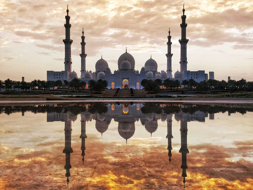 Majestic Reflections of Shaik Zayed Grand Mosque and fiery golden sky captured from the Oasis of Dignity, Abu Dhabi, UAE.     The Oasis of Dignity has still water at it's center which gives you splendid reflections of the mosque during mornings and evenings. A good place to find fellow travel & professional photographers clicking those reflections!