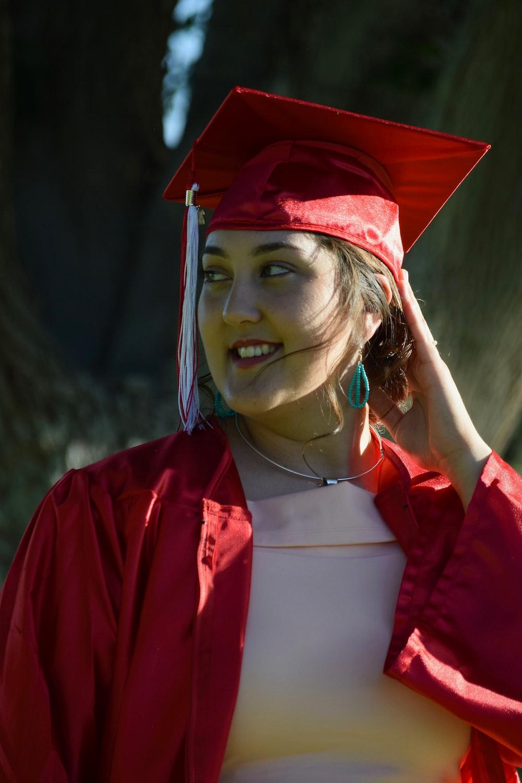 woman wearing red academic dress smiling