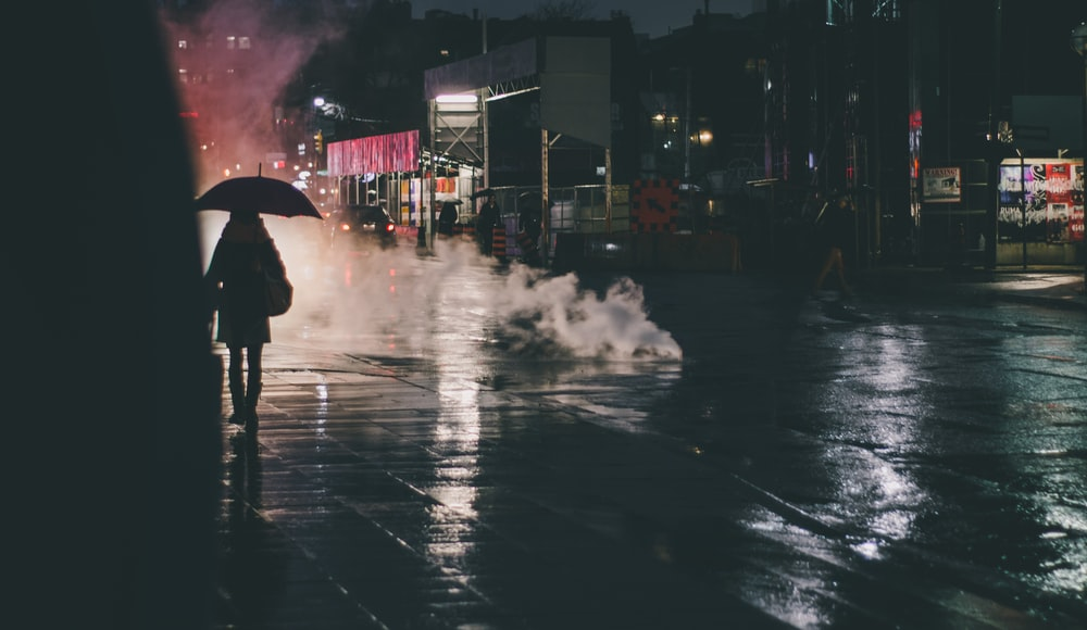silhouette photography of person walking holding umbrella