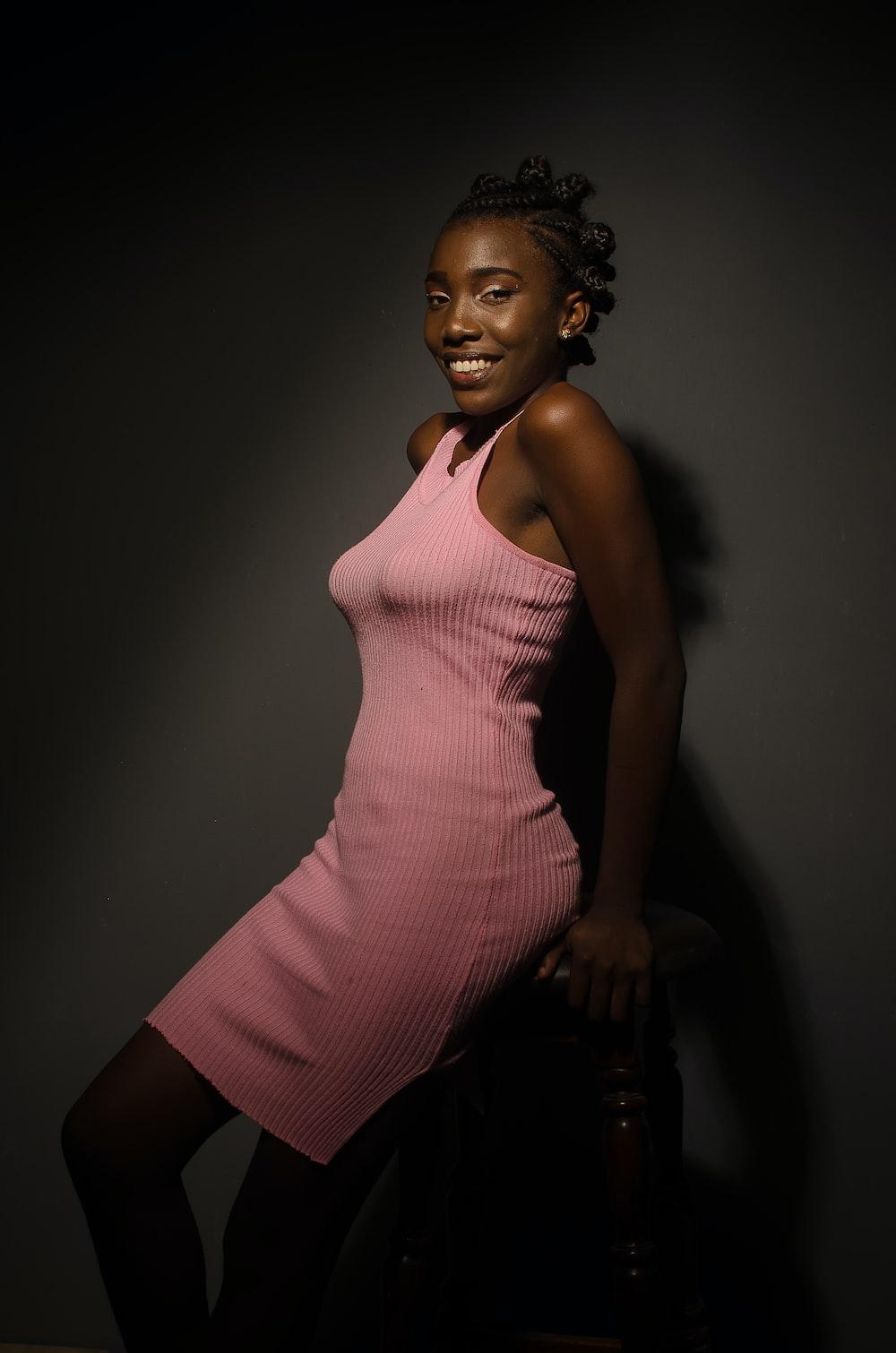 smiling woman in pink sleeveless midi dress