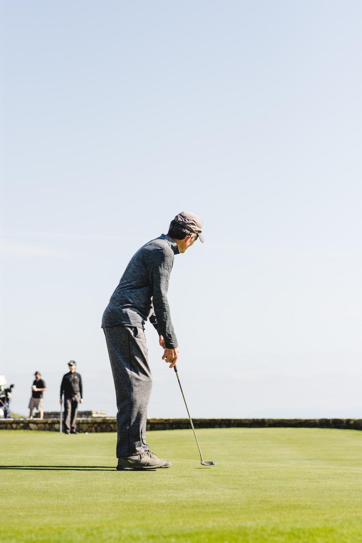 man playing golf in green fields