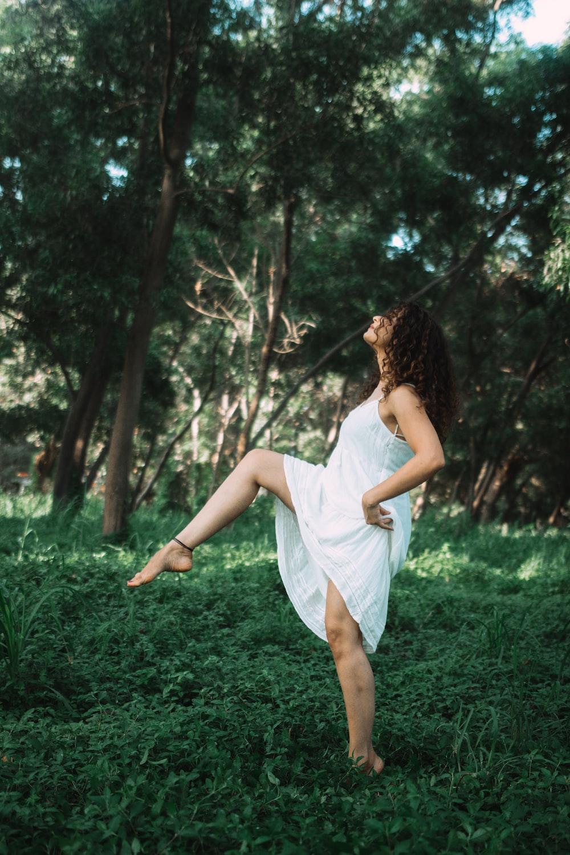 woman walking on green grass near trees