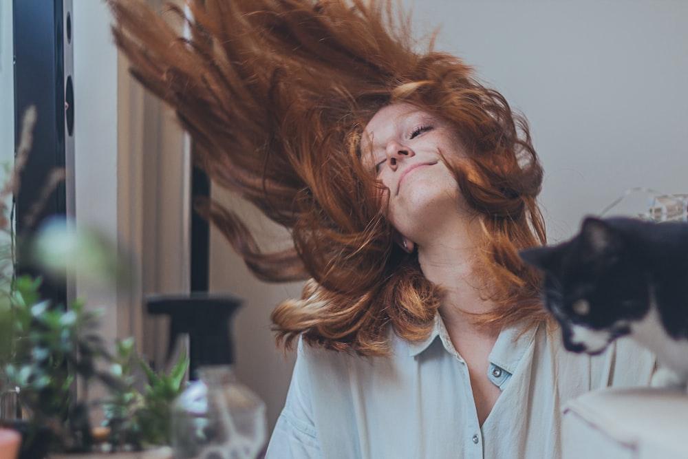 woman in teal dress shirt flipping brown hair