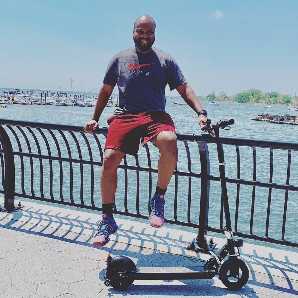 man sitting on railing near kick scooter