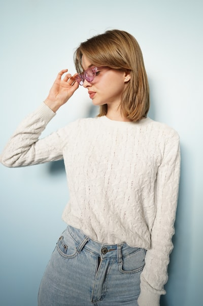 A beautiful model with glasses in a sweater and jeans, blue background