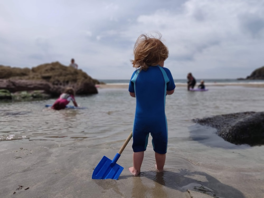 toddler holding plastic spade on shore