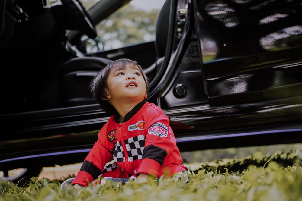 boy sitting on grass in front of parked car